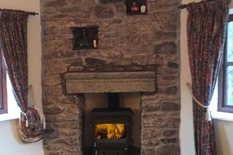 Woodwarm stove in a traditional stone fireplace