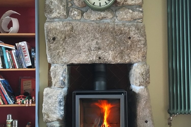 Stuv 16 cube in traditional stone fireplace